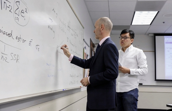 Dr. James Prieger writing on white board teaching School of Public Policy Student Aotian